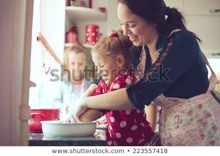 mother baking a cake with her children stock photo © konradbak