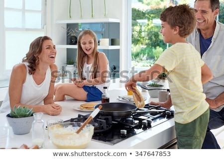 glimlachend · familie · eettafel · moeder · permanente · portret - stockfoto © is2