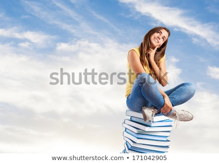 Young Indian girl student sits on stack of books Stock photo © vectorikart