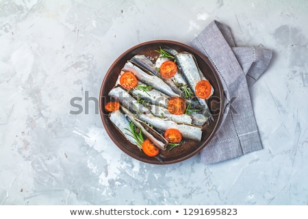 Stock photo: Sardines or baltic herring with parsley and tomatoes slices on c