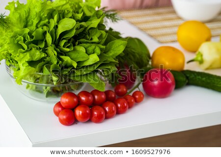Ripe tomatoes with green stems and fresh spinach leaves on a blue background with a reflection of th Stock photo © artjazz
