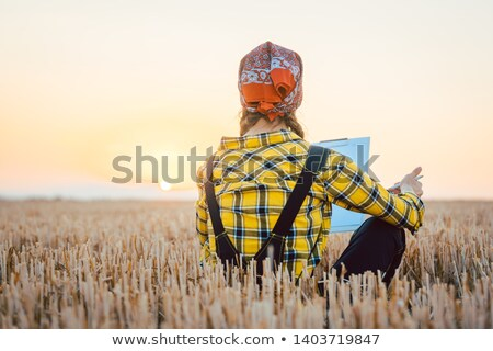 Farmer woman calculating harvest yield after a long day Stock photo © Kzenon