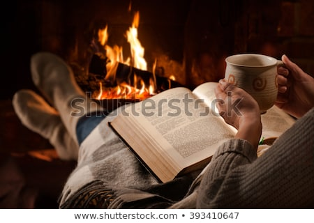Woman resting with a book near fireplace stock photo © doodko
