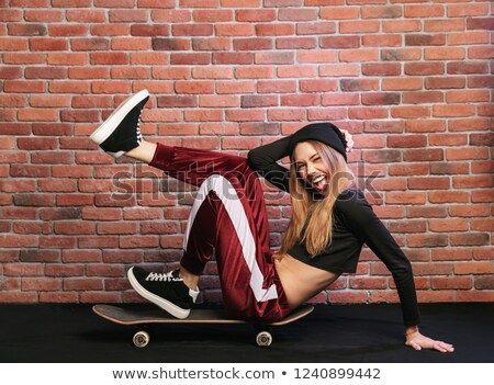 Photo of cheerful sporty girl 20s, laughing while sitting on ska Stock photo © deandrobot