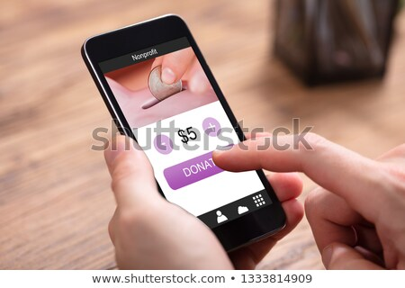 Businessperson Donating Money Online On Mobile Phone Stock photo © AndreyPopov