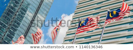Flags of Malaysia against the background of skyscrapers Stock fotó © galitskaya