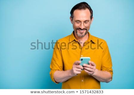Portrait of happy bearded man wears fashionable clothes uses ska Stock photo © vkstudio