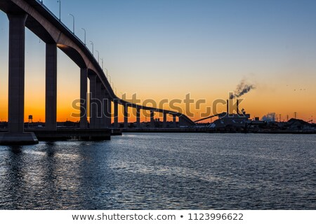 industrial ship and factory silhouetted at sunset stock photo © kawing921