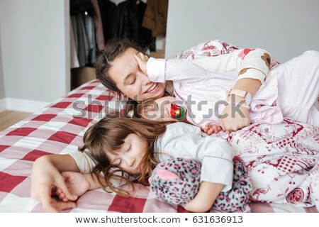 Smiling brunette woman lying while her baby is sleeping in a bedroom Stock photo © wavebreak_media