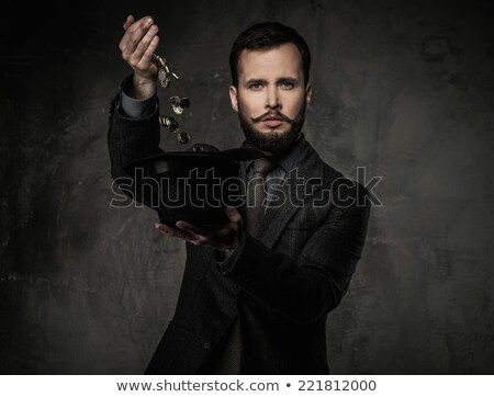 Handsome well-dressed man in jacket with hat full of coins Stock photo © Nejron