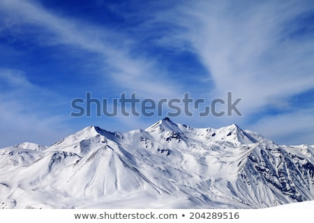 Snowy mountains in clouds and off-piste slope Stock photo © BSANI