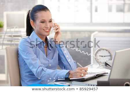 Young pretty woman talking on the phone and makes notes in a not Stock photo © vlad_star