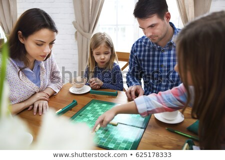 Happy young family plaing board game Stock photo © dashapetrenko