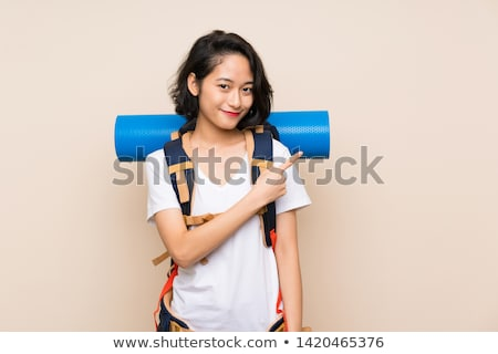 Asian traveler pointing to the side. Stock photo © RAStudio