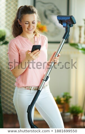 woman using mobile phone and cleaning with vacuum cleaner stock photo © deandrobot
