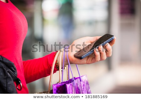 Close-up shot of woman using cellphone in the street. Stock photo © deandrobot