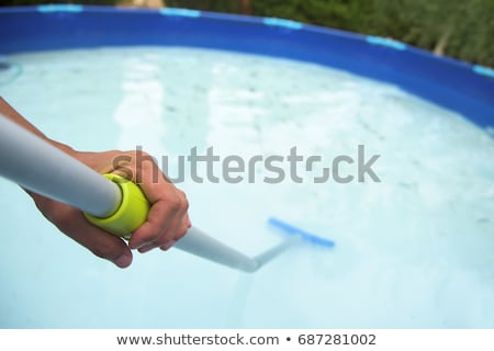 young man cleaning a portable swimming pool Stock photo © nito