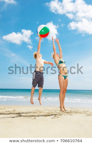 Young couple leaping for beach ball Stock photo © IS2