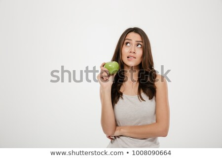 Portrait of puzzled woman looking upward holding green fresh app Stock photo © deandrobot