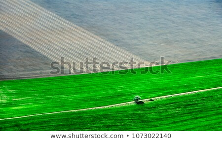 Top view of green tractor plowing the ground after harvesting on the field in the autumn time. Top v Stock photo © artjazz