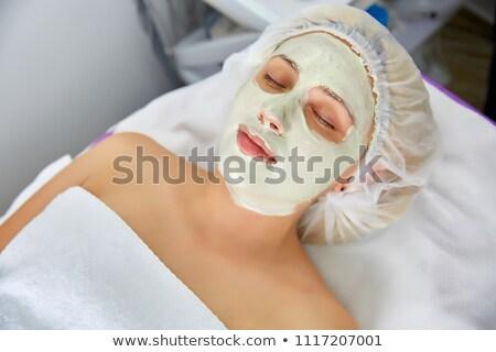 Beautician applying face peeling mask to woman Stock photo © Kzenon
