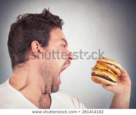 Hebzuchtig man eten hamburger portret jonge man Stockfoto © AndreyPopov