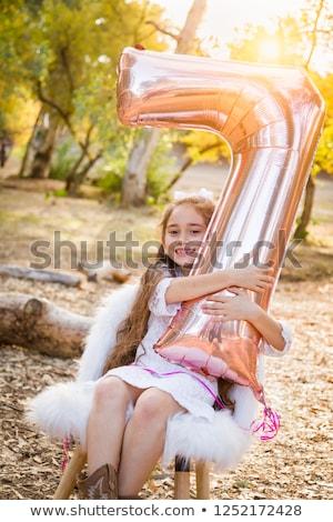 Bonitinho jovem jogar número sete balão Foto stock © feverpitch