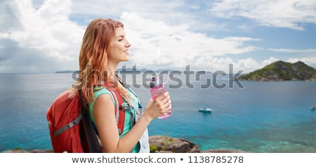 happy woman with backpack over seychelles island stock photo © dolgachov