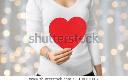 woman with gay awareness wristband holding heart Stock photo © dolgachov