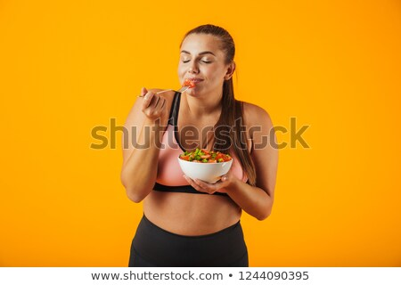 Image of lovely chubby woman in tracksuit eating green salad fro Stock photo © deandrobot