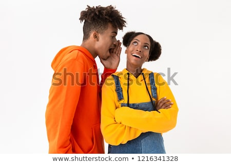 Photo of african american man talking secrets in ear of his girl Stock photo © deandrobot