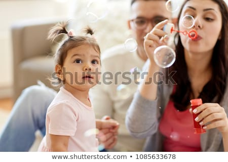 father and baby daughter with soap bubbles at home Stock photo © dolgachov