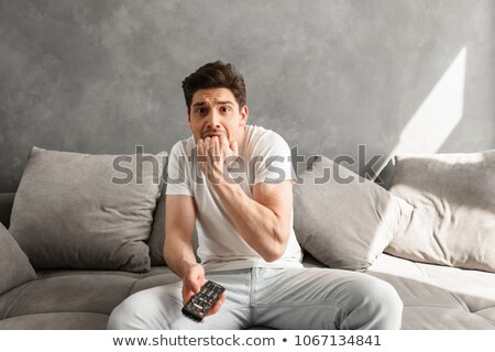 Photo of scared man biting his fist in fear while sitting on cou Stock photo © deandrobot