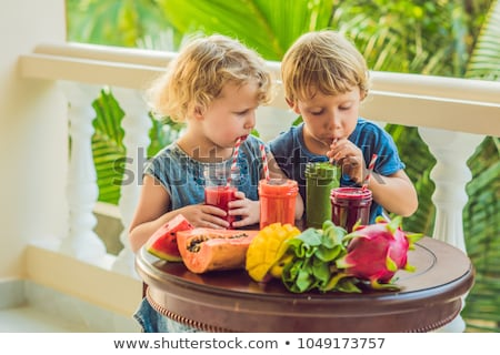 Children drink colorful healthy smoothies.. Watermelon, papaya, mango, spinach and dragon fruit. Smo Stock photo © galitskaya