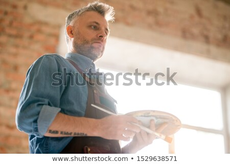 pensive or serious middle aged man in workwear thinking of ideas at work stock photo © pressmaster