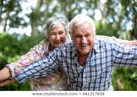 front view of happy senior man looking at camera while senior women are standing behind in garden stock photo © wavebreak_media