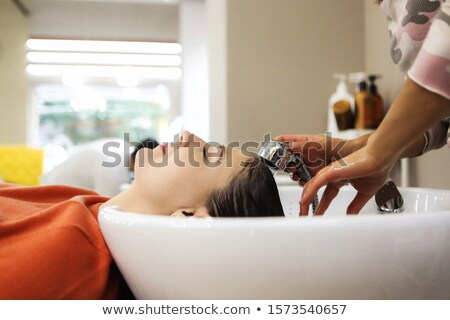 Cheerful young woman enjoying head massage while getting her hai Stock photo © dashapetrenko