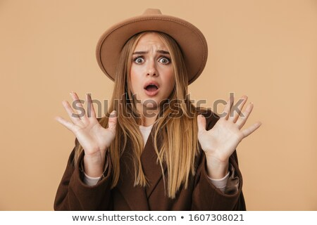 Image of scared girl wearing hat raising her arms and screaming  Stock photo © deandrobot