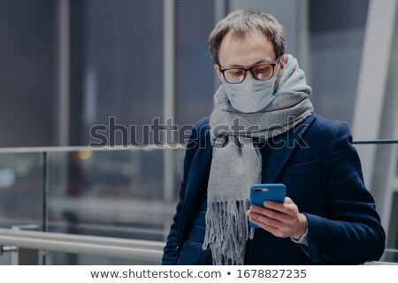 Photo of man watches news on his phone, wears protective mask, protects from air contamination or co Stock photo © vkstudio