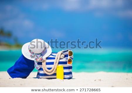 beach bag, sunscreen, sunglasses and hat on sand Stock photo © dolgachov