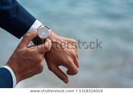 Young businessman looking at his watch Stock photo © photography33