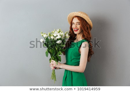 smiling redhead woman in dress holding flowers stock photo © deandrobot