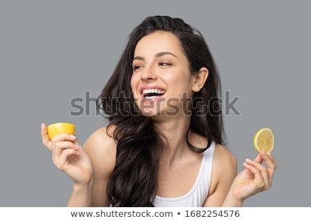 Beautiful fitness woman holding an orange Stock photo © restyler