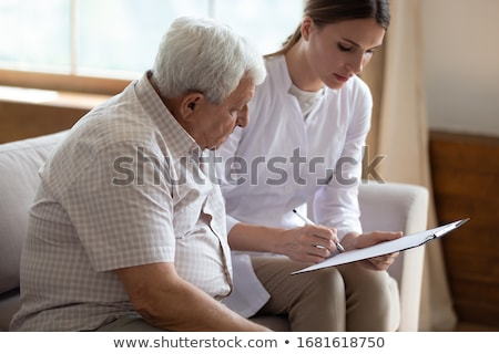 Female doctor writing notes during patient's medical exam Stock photo © stevanovicigor