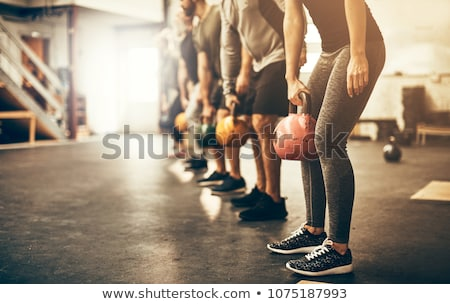 Fitness woman working out with kettle bell Stock photo © Yatsenko