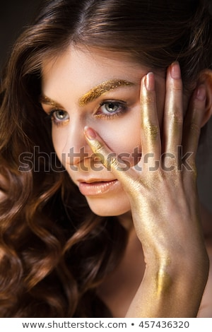 Fashion model with eyebrow and hand covered in gold Stock photo © julenochek