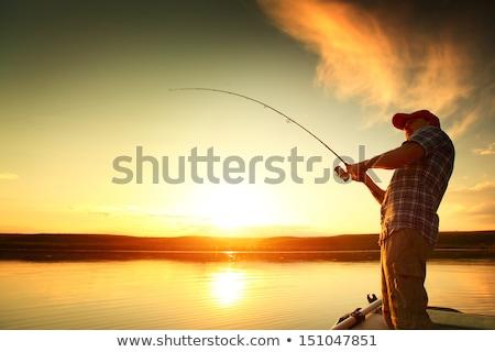 Young man fishing at sunset Stock photo © IMaster