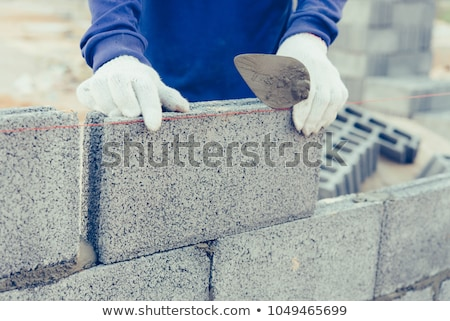 bricklayer worker installing brick masonry on exterior wall with stock photo © milsiart