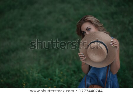 Beautiful young woman in a wide-brimmed straw hat that covers he Stock photo © TanaCh