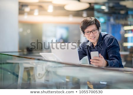 A young man with glasses and headphones is working at the computer. Before the guy is a magnetic boa Stock photo © Traimak